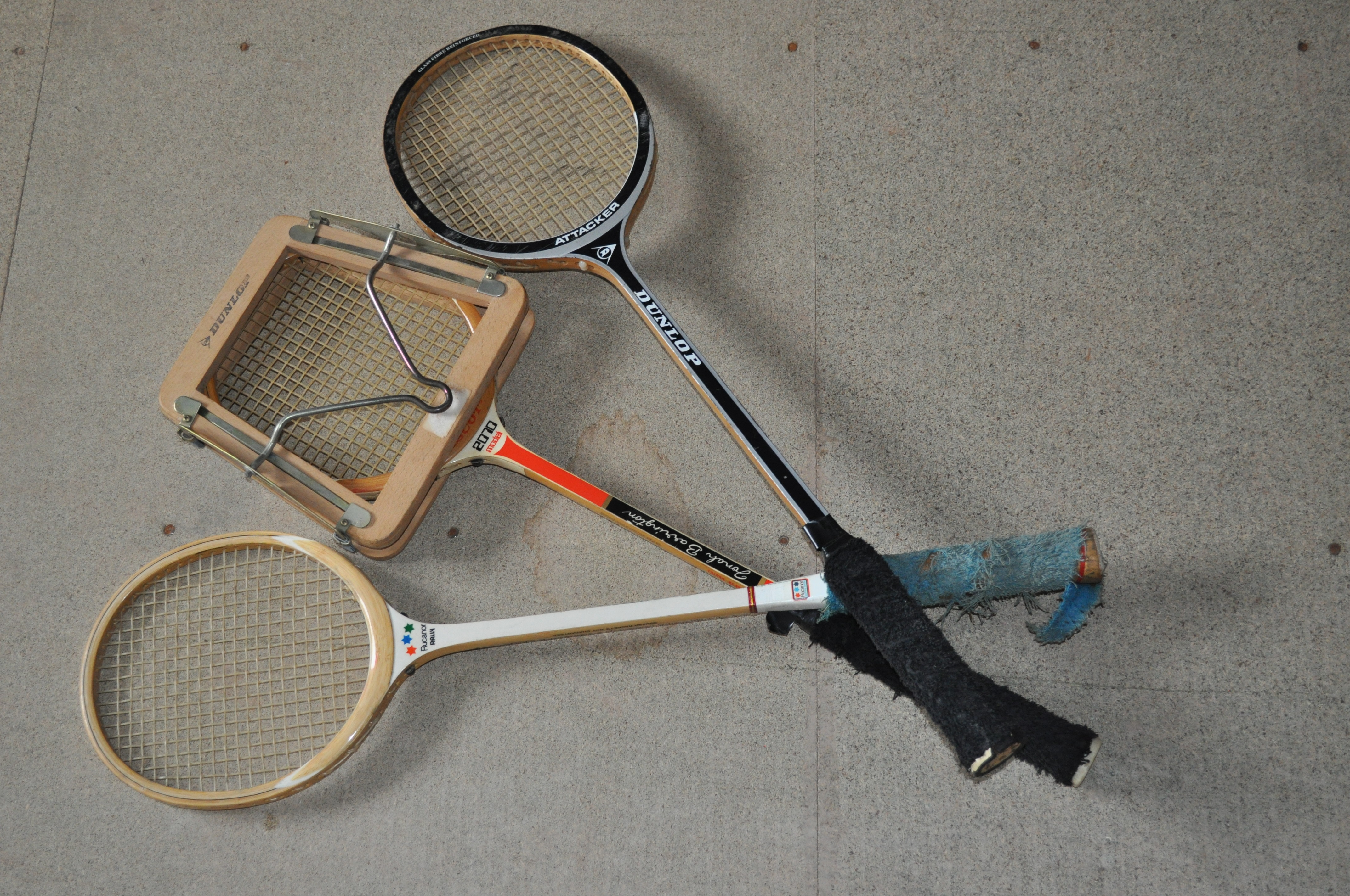 Three wooden rackets, one with racket press